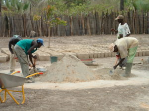 Hand mixing sand and cement for the blocks